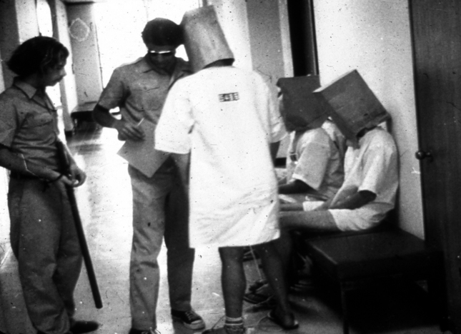 """Guards"" talk to ""prisoners"" during the 1971 Stanford Prison Experiment.  At one point, bags were put over ""prisoners' "" heads and ""prisoners"" were moved in response to rumors about a prison break being planned. Courtesy of Phil Zimbardo"